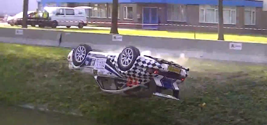 The rally car then pirouettes mid in the air and lands on its roof